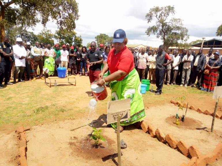 Sendeza watering a tree after planting it.