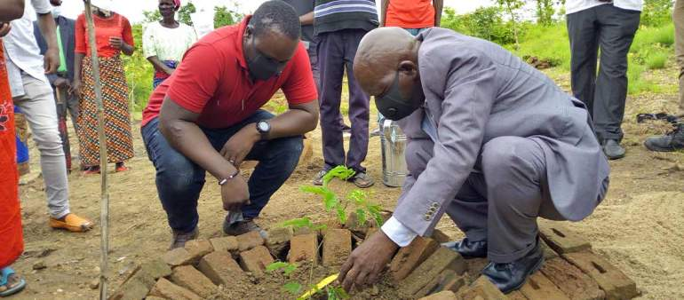 MP Kaphamthengo Yona (in suit) planting a tree as DFO Jason looks on