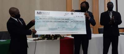 Dr Usi (L) receiving a cheque from Malawi gaming board representatives