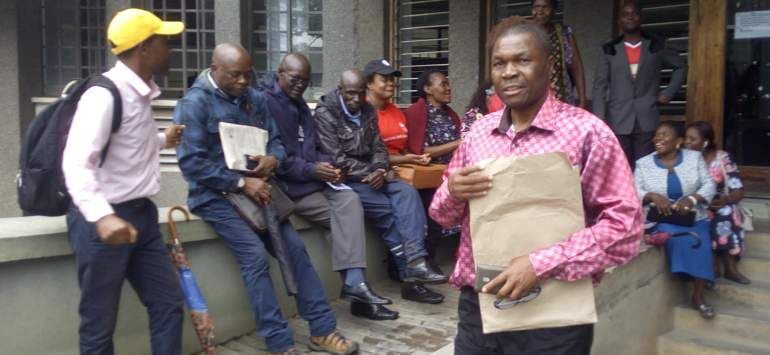 Malimba (carrying envelope) at the DC's office in Blantyre