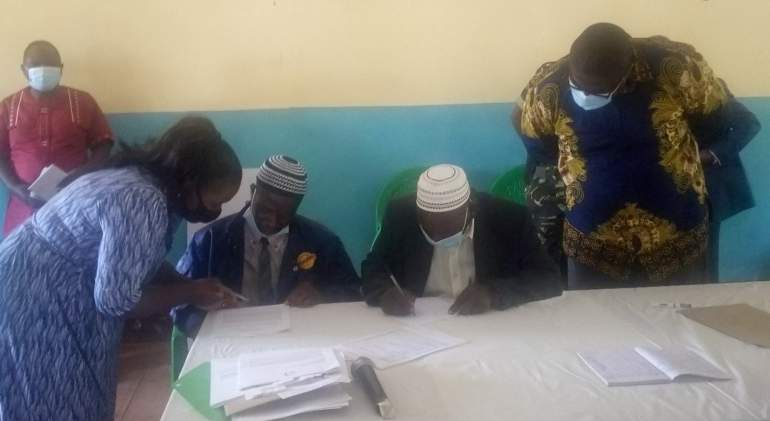 Tukamulane members signing for the grant, while Jere left and Kachale (right) witnessing