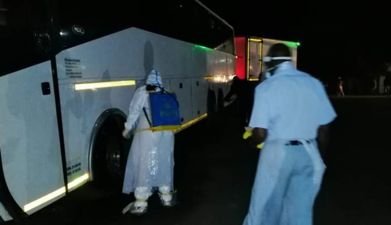 Health workers disinfecting the bus upon arrival at the border