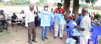 Ajawa (in mask) presenting a football jersey to Area 49 Market Rangers officials