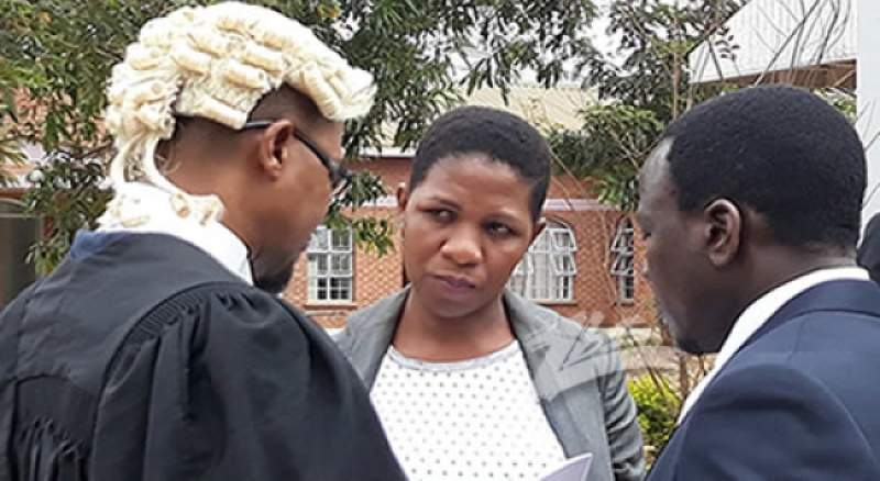 Gwalidi (middle) interacting with Chilima's lawyer at the court