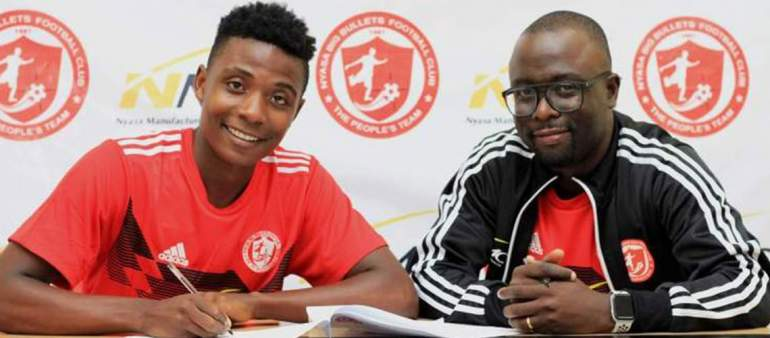 Banda putting pen to paper, while Bullets CEO Escort Chinula looks on