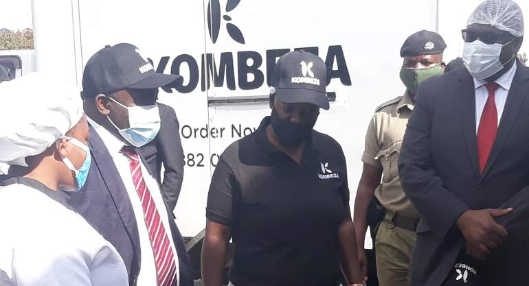 Kachale (in red neck tie) visiting Kombeza factory